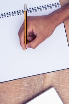 Geerntetes bild des geschäftsmannschreibens auf buch am schreibtisch