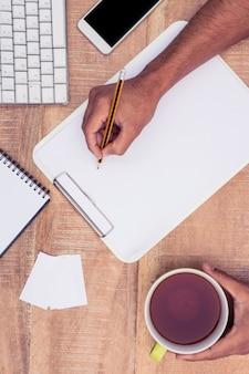 Geerntetes bild des geschäftsmannschreibens auf notizbuch am schreibtisch beim halten des kaffees im büro