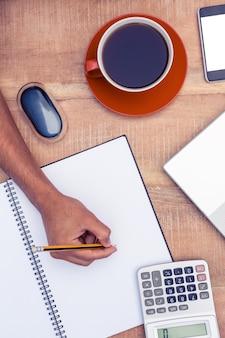 Geerntetes bild des geschäftsmannschreibens auf notizbuch durch kaffee am schreibtisch im büro