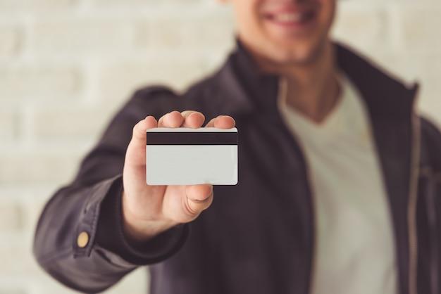 Geerntetes bild des hübschen kerls eine kreditkarte halten.