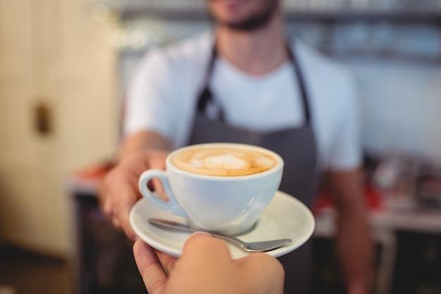 Geerntetes bild des kunden kaffee vom kellner am café nehmend