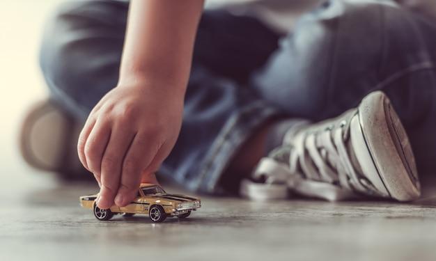 Geerntetes bild des netten kleinen jungen, der mit spielzeugauto spielt.