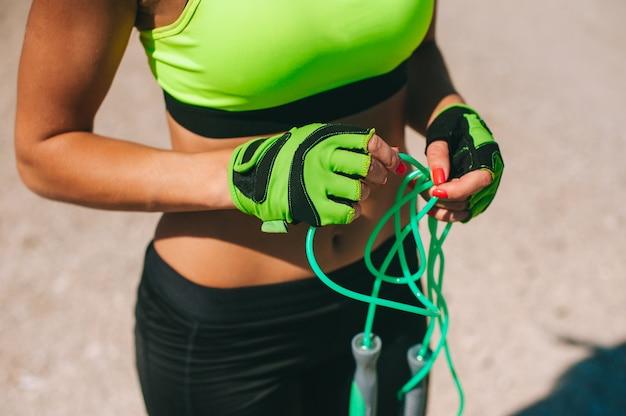 Geerntetes bild des sportmädchens in den schweißhosen und -turnschuhen welche springende seil in der morgensonne