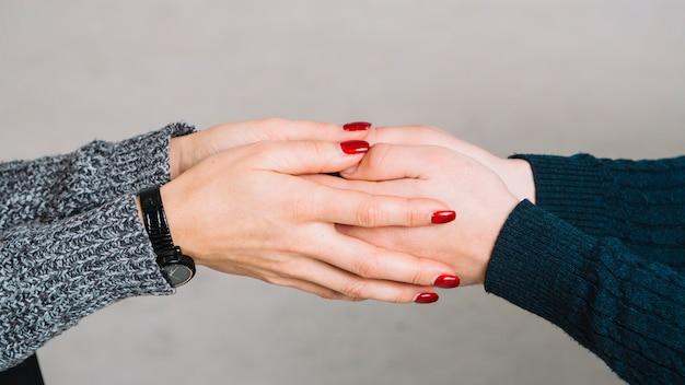 Geerntetes bild des weiblichen psychologen die hände ihres kunden gegen grauen hintergrund halten