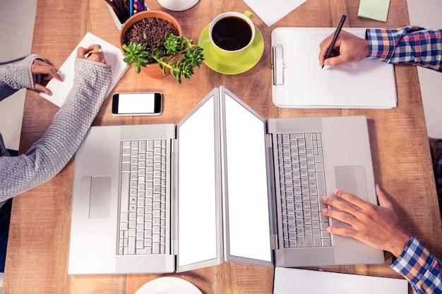 Geerntetes bild von den geschäftsleuten, die an schreibtisch im kreativen büro arbeiten