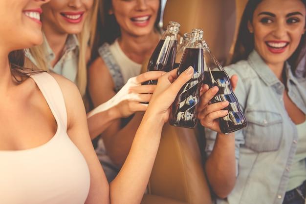 Geerntetes bild von den schönen stilvollen mädchen, die gläser klappern.