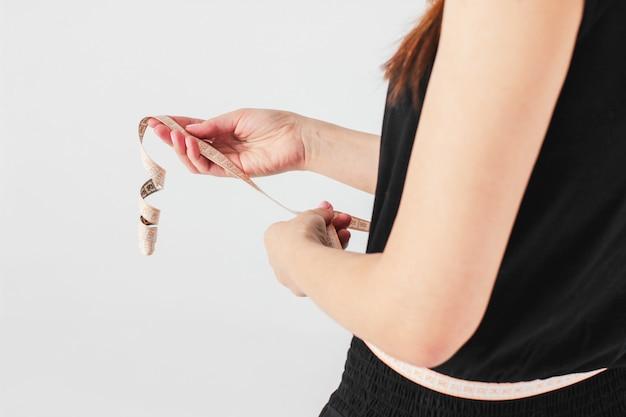 Geerntetes foto des frauenmädchens misst die taille im schwarzen yoga jum