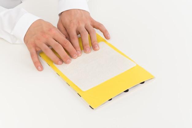 Geerntetes foto von händen eines mannes, der blindenschrift liest