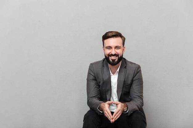 Geerntetes porträt des entspannten mannes stillstehend beim sitzen auf stuhl im büro und lächeln auf der kamera, welche die hände zusammenfügt, lokalisiert über grau