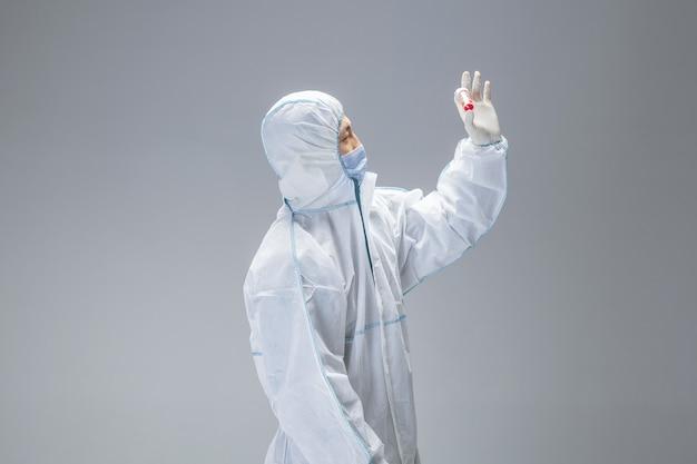 Gefährlich. sanitäter im weißen hazmat-schutzanzug, der blut auf der suche nach epidemischem virus, lungenentzündungs-atemwegssymptomen überprüft und scannt. chinesische coronavirus-abbildung. gesundheitswesen, medizinkonzept.