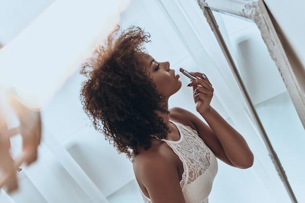 Gefährlich schön. blick von oben auf die attraktive junge afrikanerin, die zu hause vor dem spiegel lippenstift aufträgt