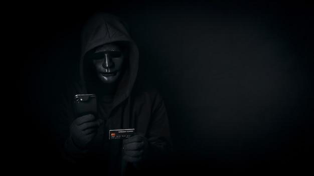Gefährliche anonyme hacker benutzen smartphone und kreditkarte, brechen sicherheitsdaten und hacken passwort