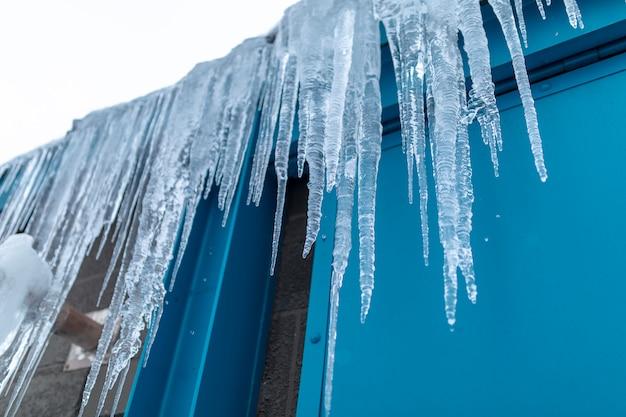 Gefährliche eiszapfen, die vom dach im winter im hokkaido, japan hängen