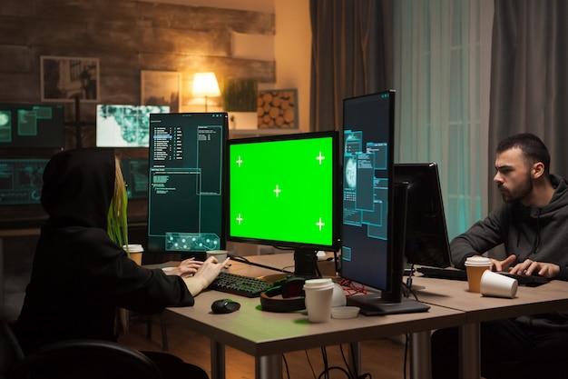 Gefährliche hackerin beim schreiben einer malware auf dem computer mit grünem bildschirm. männlicher hacker.
