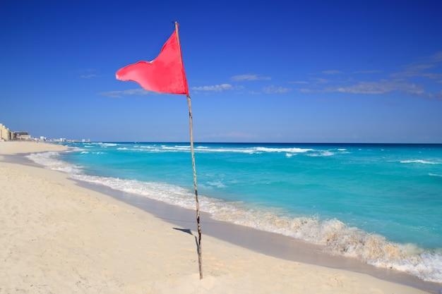 Gefährliche rote fahne im rauen seesignal des strandes