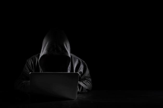 Gefährlicher anonymer hacker-mann in schwarzer kapuze mit computer, der in den sicherheitsdaten-unternehmensserver einbricht. er sitzt und arbeitet am schwarzen hintergrund. internetkriminalität, sicherheitskonzept für cyberangriffe