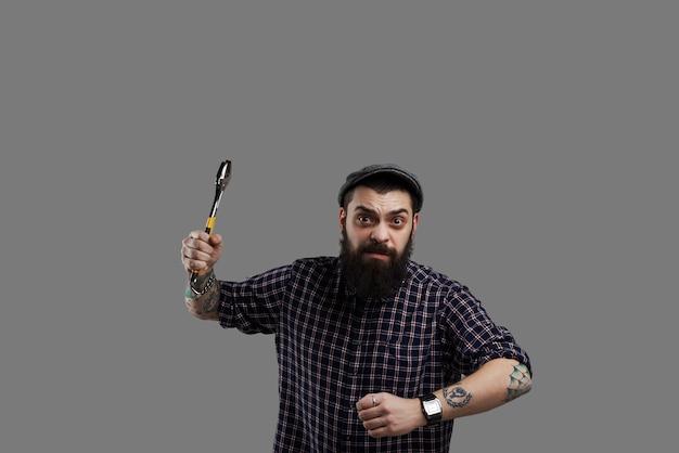 Gefährlicher bart-hipster mit tätowierten händen und schraubenschlüssel. verrückter mann läuft mit aggressivem gesicht in die kamera. angstkonzept.