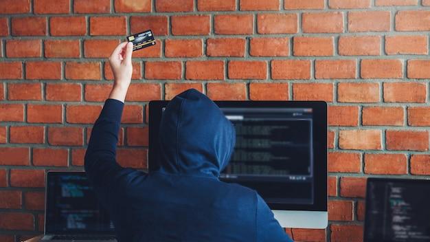 Gefährlicher mit kapuze hacker, der die kreditkarte verwendet, die schlechte daten in computeron-line-system schreibt und zu den globalen gestohlenen persönlichen informationen verbreitet. cyber-sicherheitskonzept