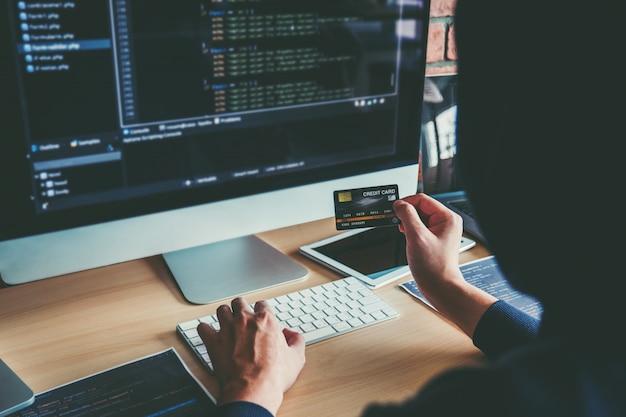 Gefährlicher mit kapuze hacker, der die kreditkarte verwendet, die schlechte daten in computeron-line-system schreibt und zu den globalen gestohlenen persönlichen informationen verbreitet. onlinesicherheit
