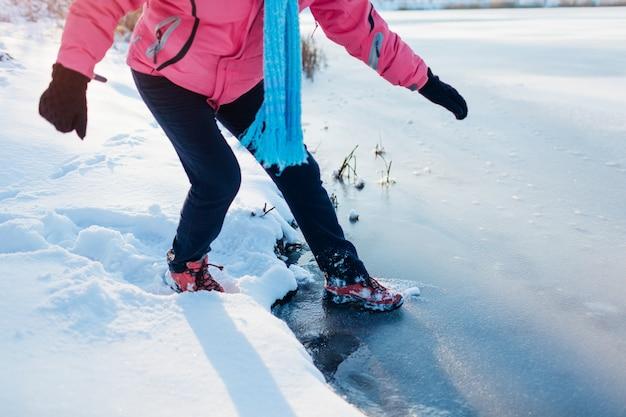 Gefährliches dünnes eis. frau geht risiko ein, auf gefrorene flussoberfläche im winter zu treten. vorsicht, unsicheres wasser, fallmöglichkeit
