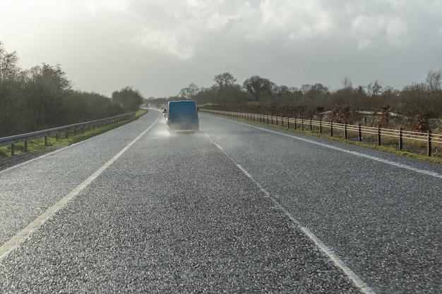 Gefährliches fahrzeug, das in der stark regnerischen und rutschigen straße fährt. abstraktes verschwommenes schlechtes wetterauto auf der autobahn.