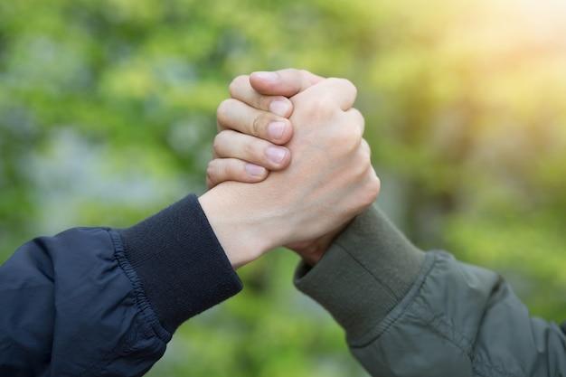 Gefährtenhand umklammert erfolgsvertrauen, selbstbewusstes konzept. oder nahaufnahme einer geschäftshand zwischen zwei kollegen auf parks.