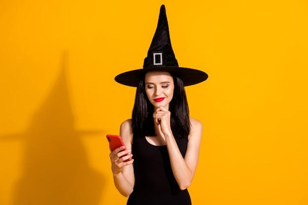 Gefälscht oder nicht. foto der süßen charmanten jungen magierdame handkinn halten telefon denken online-nachrichten lesen tragen schwarzes zauberer-kopfbedeckungskleid isoliert hellgelber farbhintergrund