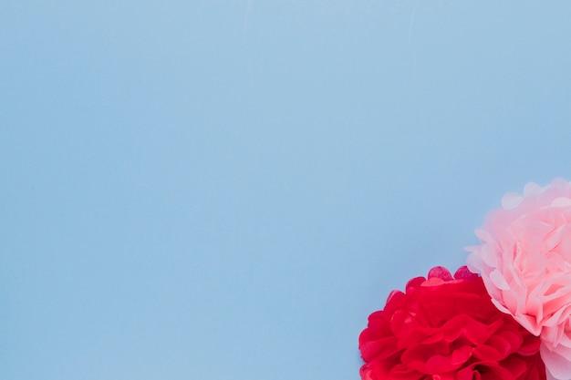 Gefälschte rosa und rote schöne dekorative blumen an der ecke des blauen hintergrundes