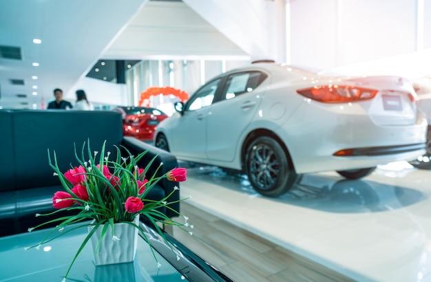 Gefälschte rote blumen in der weißen keramikvase auf unscharfem hintergrund. autohändler. verschwommenes luxusauto im ausstellungsraum geparkt. automobilindustrie.