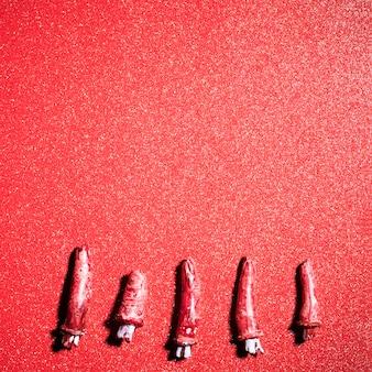 Gefälschte unheimliche finger über rotem glitzerhintergrund