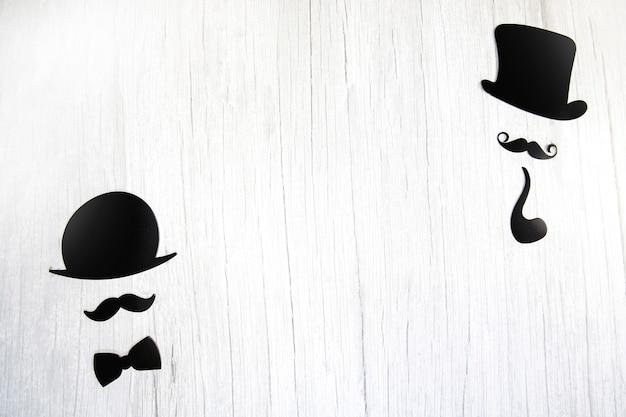 Gefälschter schnurrbart, krawattenschleife und hut auf weißem holzhintergrund. internationaler männertag und vatertagskonzept flache lage, draufsicht, kopierraum