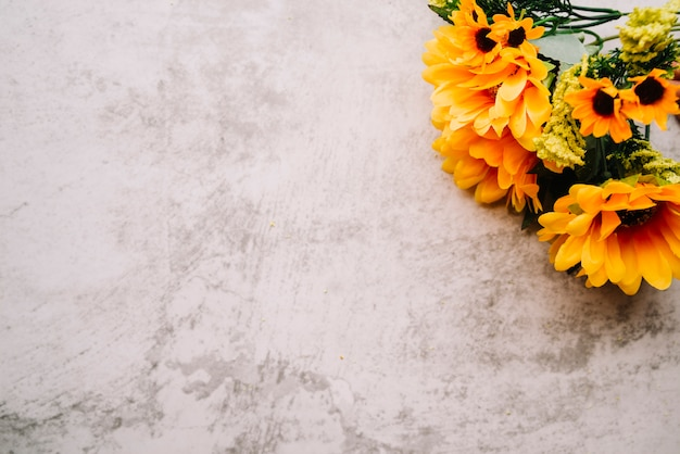 Gefälschter sonnenblumenblumenstrauß auf einer alten weißen wand