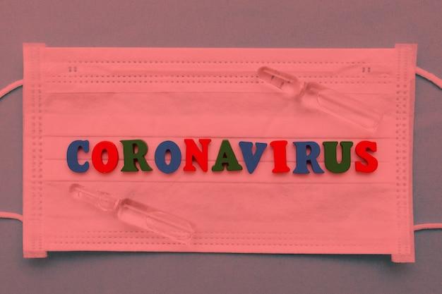 Gefahr des coronavirus. die inschrift von buchstaben auf einer medizinischen weißen maske und einer ampulle mit einer medizin in rot