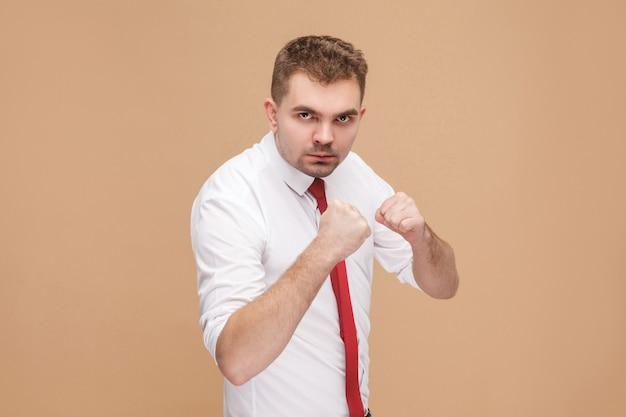 Gefahr und starker geschäftsmann, der boxzeichen zeigt und bereit ist zu kämpfen. geschäftsleute konzept, gute und schlechte emotionen und gefühle. studioaufnahme, isoliert auf hellbraunem hintergrund