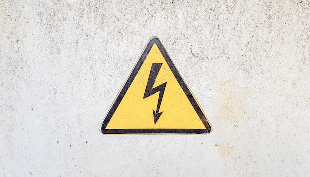 Gefahrenzeichen für hochspannungsstrom. gelbes dreieckiges schild mit einem blitz in der mitte. diese warnung steht auf einer alten, mit grauer farbe bemalten metalloberfläche.