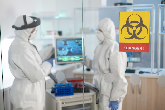 Gefahrenzonenschild im medizinischen labor und wissenschaftler arbeiten