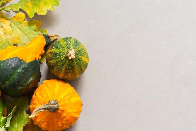 Gefallene blätter von bäumen und orange dekorativen kürbissen auf einem grauen hintergrund, herbsthintergrund