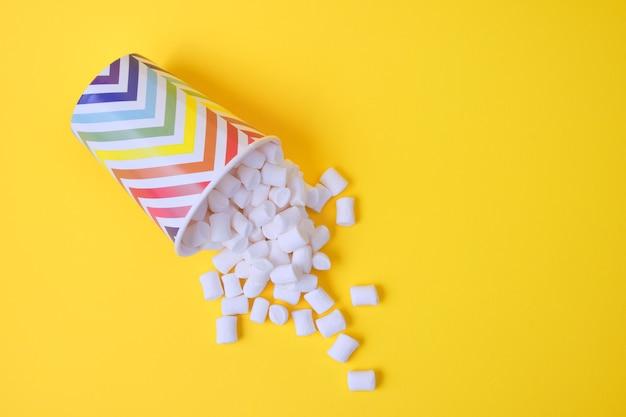 Gefallene marshmallows in papierferienglas mit geometrischem muster auf gelbem hintergrund