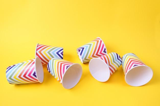 Gefallene papierbecher mit geometrischem muster auf gelbem hintergrund