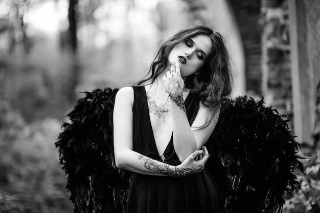 Gefallener engel mit schwarzen flügeln im alten wald