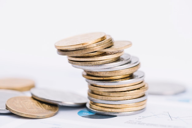 Gefallener stapel münzen auf weißem hintergrund über dem diagramm