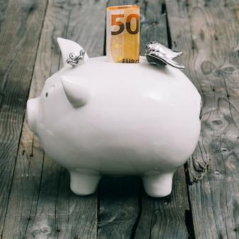 Gefaltete anmerkung des euro fünfzig im schlitz des weißen sparschweins auf holztisch