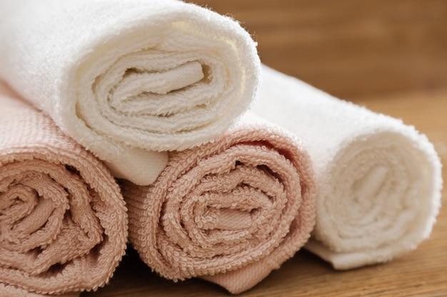 Gefaltete badetücher rosa und weiß gefärbt auf holztisch für hotelbadekurort. flauschige handtücher reinigen. nahansicht.
