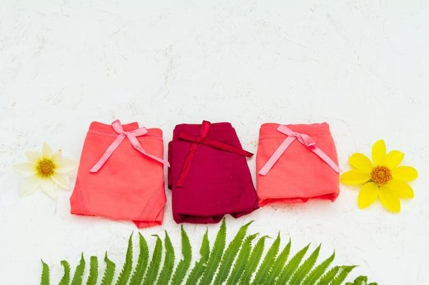 Gefaltete baumwollhöschen unterschiedlicher farbe mit gelben blütenknospen und einem farnblatt auf weißem hintergrund. damenunterwäsche eingestellt. ansicht von oben.