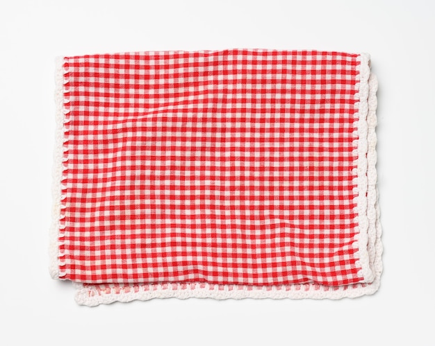 Gefaltete baumwollrot-weiß karierte serviette auf weißem hintergrund