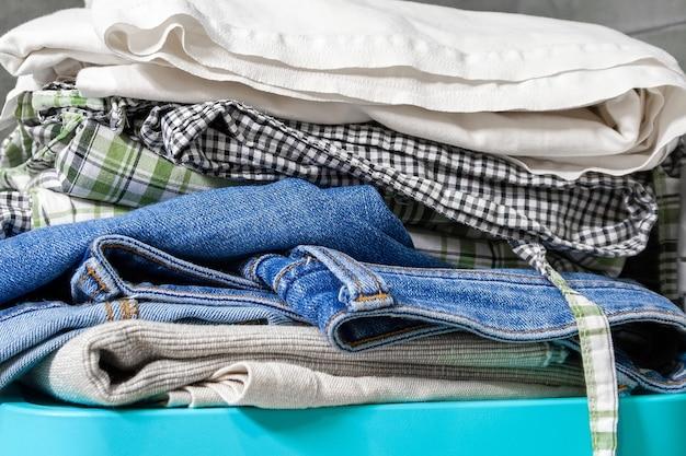 Gefaltete bettwäsche, jeans, handtücher auf einer blauen box. stapel wäsche und kleidung zum waschen vorbereitet. nahaufnahme
