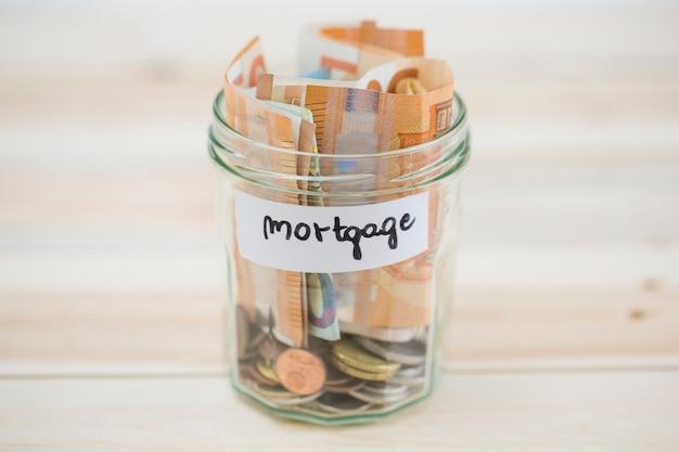 Gefaltete euroanmerkungen und -münzen im hypothekenglasgefäß auf hölzernem hintergrund