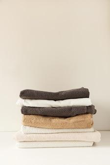 Gefaltete handtücher stapeln sich auf weiß. gesundheitswesen, hygiene, wellness-zusammensetzung