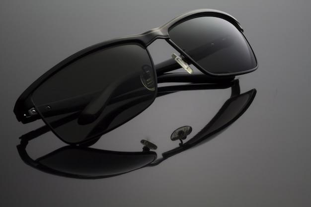 Gefaltete schwarze sonnenbrille auf schwarz