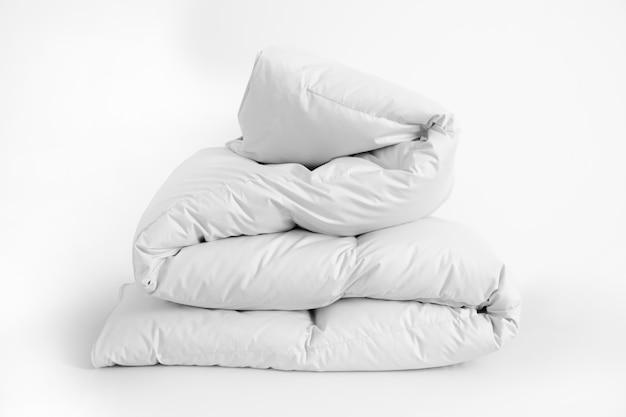Gefaltete weiche weiße bettdecke, decke oder tagesdecke, gegen weißen hintergrund. nahaufnahmefoto